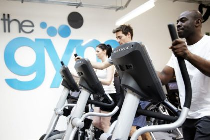 Male and female members working out on machines at The Gym Group