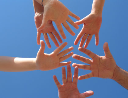 Six hands touching against a blue sky to show a sense of connection