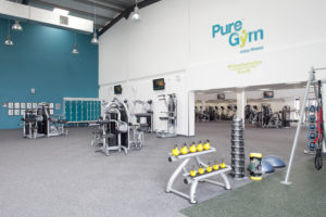 Internal view of a Pure Gym showing a range of strength machines and free hand weights