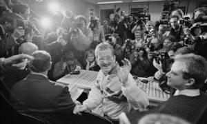 """Eddie """"The Eagle"""" Edwards waves to a large group of journalists during a press briefing"""