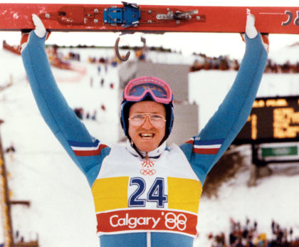 """Eddie """"The Eagle"""" Edwards holds his skis above his head"""