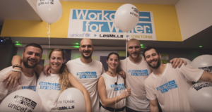 Six members of the Les Mills team smiling while wearing their 'Workout for Water' t-shirts