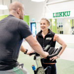 A Liikku gym personal trainer in conversation with member using an exercise bike