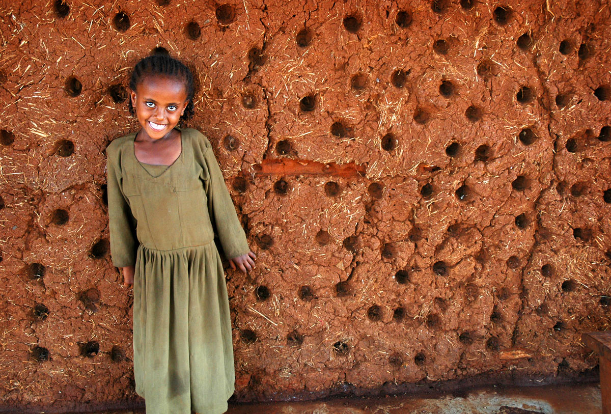 Picture of a young smiling girl against a deep brown terracotta mud wall