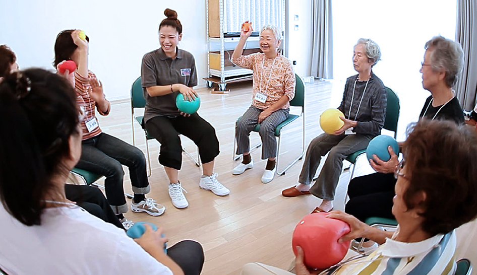 Group of older Japanese women sitting on chairs in a Genki exercise class, Japan